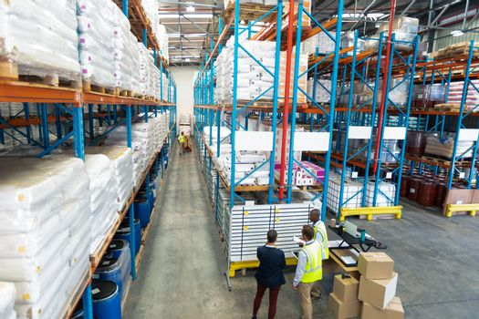 High angle view of diverse warehouse staff discussing over whiteboard in warehouse. This is a freight transportation and distribution warehouse. Industrial and industrial workers concept