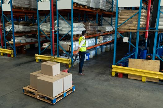 Rear view of Young Caucasian male staff using pallet jack in warehouse. This is a freight transportation and distribution warehouse. Industrial and industrial workers concept
