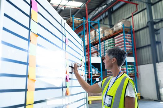 Side view of pretty mature Caucasian female staff writing on whiteboard in warehouse. This is a freight transportation and distribution warehouse. Industrial and industrial workers concept