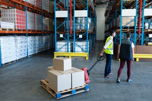 Rear view of Caucasian Male staff with his coworker using pallet jack in warehouse. This is a freight transportation and distribution warehouse. Industrial and industrial workers concept