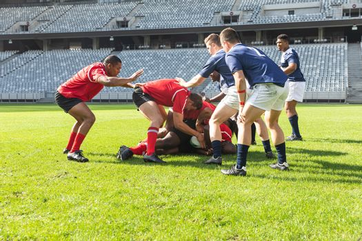 Front view of group of diverse male rugby players playing rugby match in stadium. Players are trying to get the ball from each other.