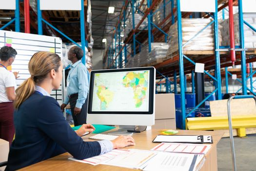Rear view of pretty mature Caucasian female manager working on computer at desk in warehouse. Diverse colleagues discussing business in front of whiteboard. This is a freight transportation and distribution warehouse. Industrial and industrial workers concept