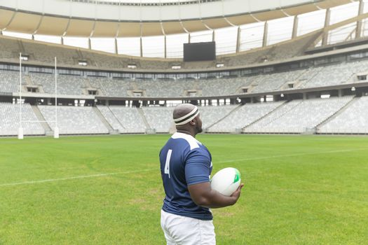 Side view of African American rugby player standing with rugby ball in the stadium