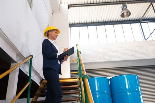 Low angle view of Caucasian female manager writing on clipboard on stairs in warehouse. This is a freight transportation and distribution warehouse. Industrial and industrial workers concept