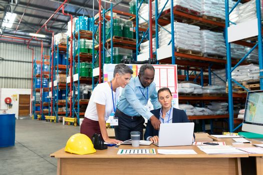 Front view of beautiful Caucasian female manager with her coworkers discussing over laptop at desk in warehouse. This is a freight transportation and distribution warehouse. Industrial and industrial workers concept