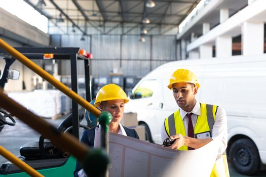 Front view of Caucasian female manager and Caucasian male supervisor discussing over inventory chart in warehouse. This is a freight transportation and distribution warehouse. Industrial and industrial workers concept