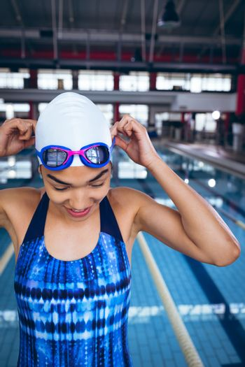 Front view of a young African-American woman wearing a swimsuit and swimming cap holding the straps of the goggles while standing by an olympic sized pool inside a stadium. Bright modern gym with fit healthy people working out and training