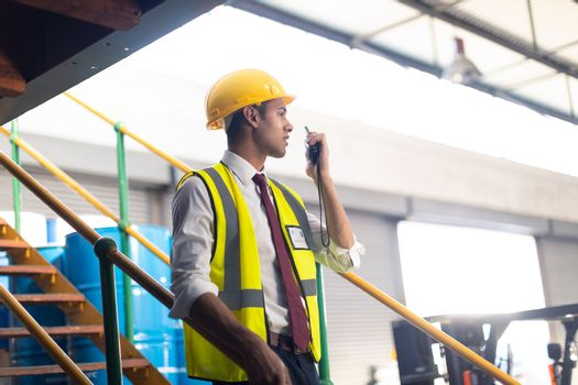 Side view of Caucasian Male supervisor talking on talkie walkie on stairs in warehouse. This is a freight transportation and distribution warehouse. Industrial and industrial workers concept