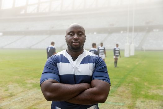 Portrait of African american male rugby player standing with arms crossed in stadium. with players in the background