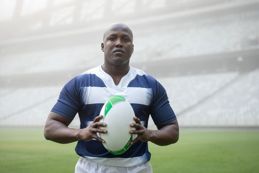 Portrait of African american male rugby player holding a rugby ball in stadium
