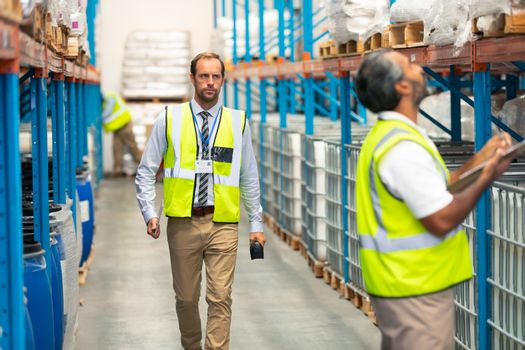 Front view of handsome Caucasian male supervisor walking in warehouse. In front of him an Asian male staff member is writing on clipboard. This is a freight transportation and distribution warehouse. Industrial and industrial workers concept