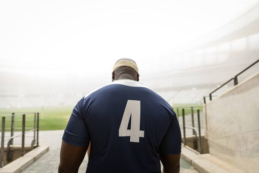 Rear view of African American male rugby player entering stadium for match