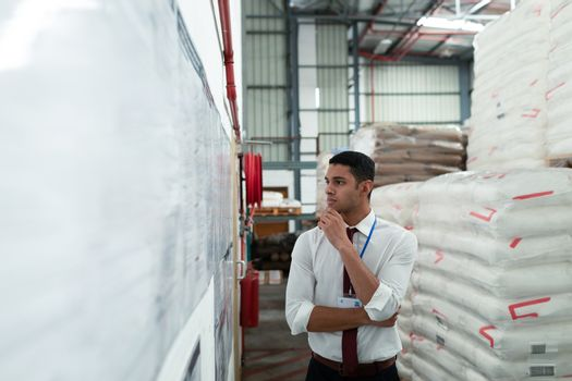 Front view of handsome young mixed-race male supervisor looking at inventory records on wall. This is a freight transportation and distribution warehouse. Industrial and industrial workers concept