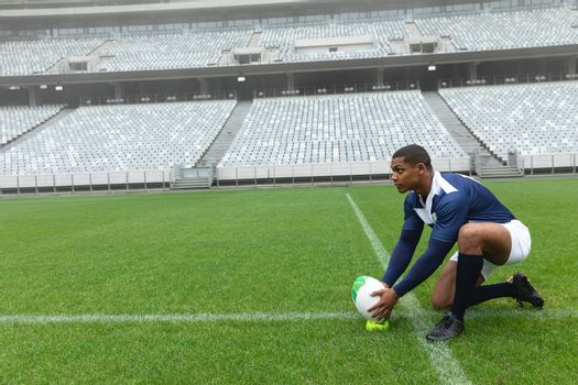 Side view of African American male rugby player placing rugby ball on a stand in stadium