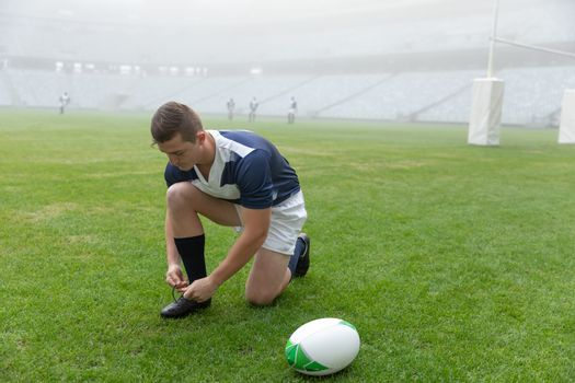 Side View of young Caucasian male rugby player tying shoelaces in the stadium. With players in the background.