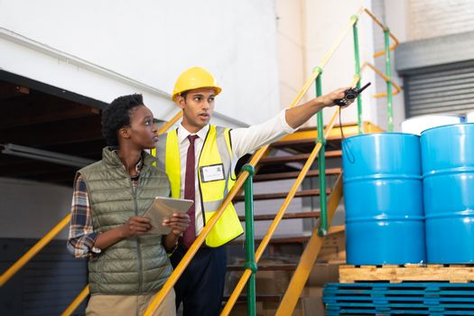 Front view of Caucasian male supervisor with African-american female worker pointing distance in warehouse. This is a freight transportation and distribution warehouse. Industrial and industrial workers concept
