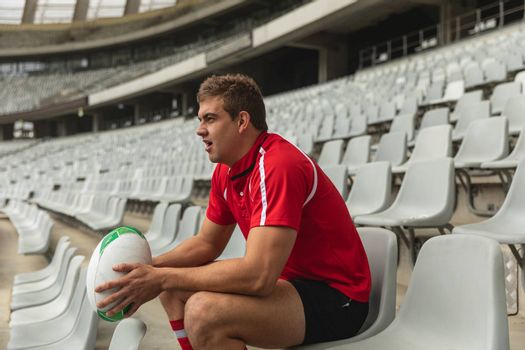 Side view of upset Caucasian male rugby player sitting with rugby ball in stadium
