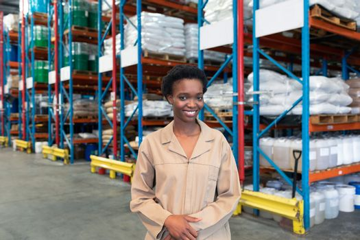 Portrait of happy young African-american female warehouse staff looking at camera. This is a freight transportation and distribution warehouse. Industrial and industrial workers concept