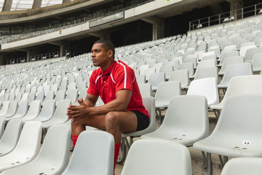 Side view of thoughtful African American male rugby player sitting alone in stadium