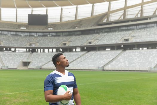 Side view of African American rugby player standing with rugby ball and looking away in stadium