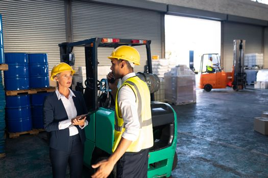 Front view of Caucasian female manager and male supervisor interacting with each other in warehouse. This is a freight transportation and distribution warehouse. Industrial and industrial workers concept