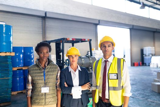 Front view of diverse warehouse staff looking at camera in warehouse. This is a freight transportation and distribution warehouse. Industrial and industrial workers concept