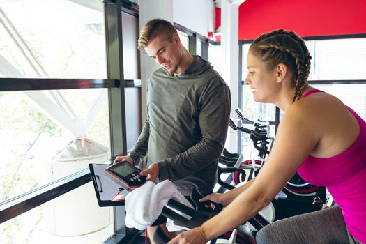 Front view of young Caucasian Male trainer assisting young Caucasian female athlete with exercise in fitness studio. Bright modern gym with fit healthy people working out and training