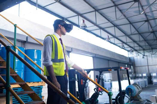 Side view of young Caucasian male supervisor using virtual reality headset in warehouse. This is a freight transportation and distribution warehouse. Industrial and industrial workers concept