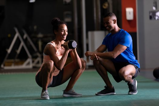 Front view of an African-American woman lifting ball weights while doing squats and an African-American man assisting her  inside a room at a sports centre. Bright modern gym with fit healthy people working out and training. Bright modern gym with fit healthy people working out and training