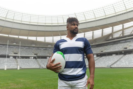 Front view of African American rugby player standing with rugby ball and looking away in stadium