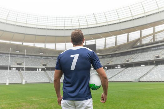 Rear view of Caucasian rugby player standing with rugby ball in stadium