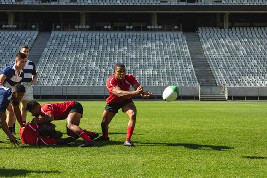 Front view of group of diverse male rugby players playing rugby in stadium. African American trying to catch the ball.