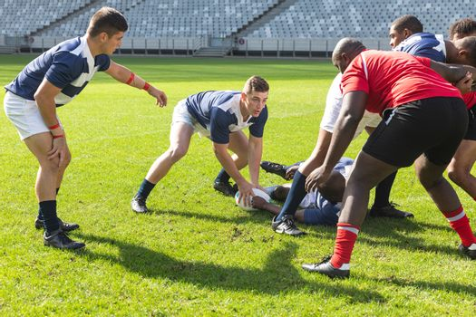Front view of Caucasian male rugby player getting the ball from African American male rugby player who is lying on the ground while diverse team surround them in stadium on sunny day.