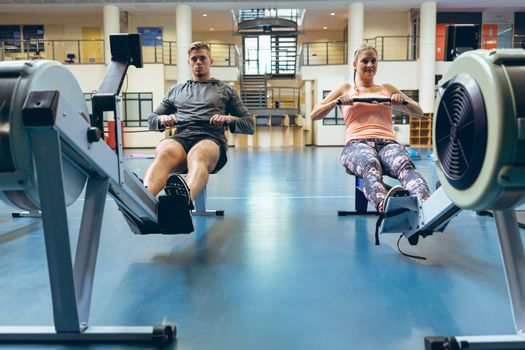 Front view of young Caucasian male and female athlete exercising with rowing machine in fitness studio. Bright modern gym with fit healthy people working out and training