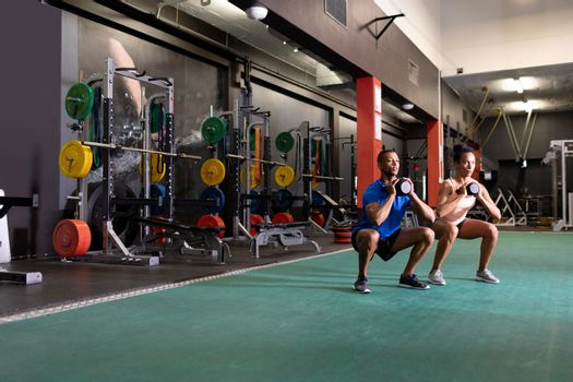 Side view of an African-American man and woman lifting ball weights with both arms while doing squats inside a room at a sports centre. Bright modern gym with fit healthy people working out and training. Bright modern gym with fit healthy people working out and training