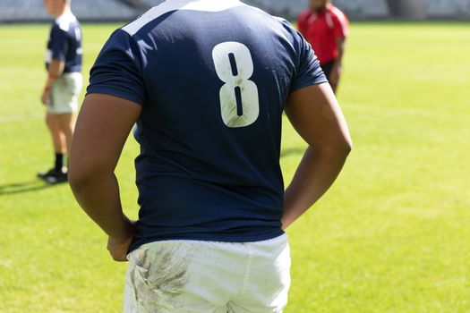 Mid section close up of handsome male rugby player standing in the stadium on a sunny day.