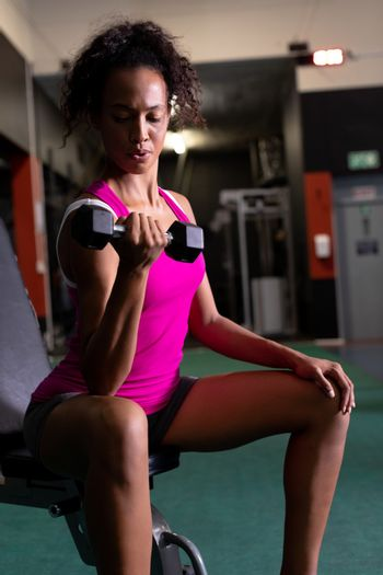 Side view of an African-American woman holding a dumbbell while sitting inside a room at a sports center. Bright modern gym with fit healthy people working out and training. Bright modern gym with fit healthy people working out and training