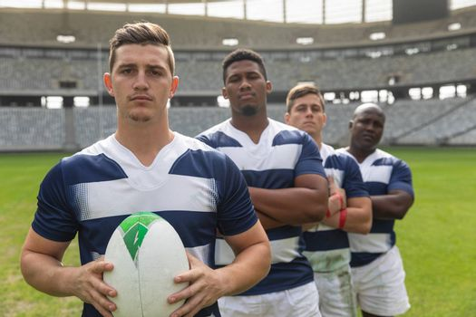 Portrait of diverse male rugby players standing with arms crossed together with rugby ball in stadium.