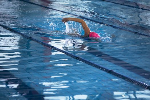 Side view of an African-American woman wearing a pink swimming cap and goggles doing a freestyle stroke in a swimming pool. Bright modern gym with fit healthy people working out and training