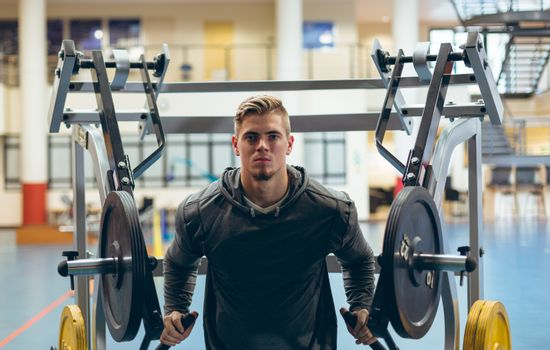 Front view of young fit Caucasian man exercising with shoulder machine in fitness studio. Bright modern gym with fit healthy people working out and training