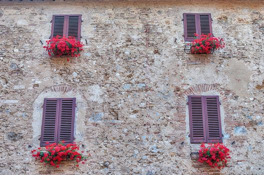 Scenic windows in the medieval architecture of San Gimignano, iconic town in the province of Siena, and one of the most visited place in Tuscany, Italy
