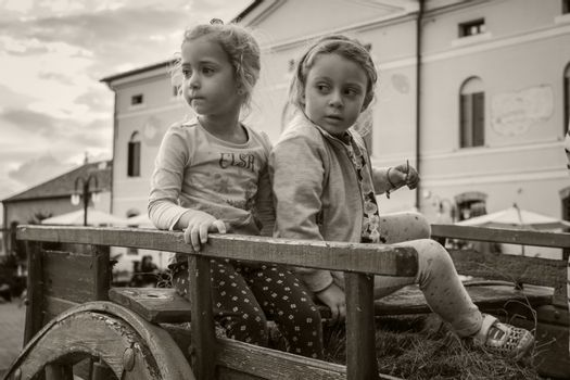 ROVIGO, ITALY 19 FEBRUARY 2020: Portrait of two little girls playing on top of an old carriage