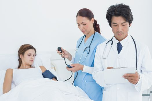 Doctor holding a medical chart as nurse checks blood pressure