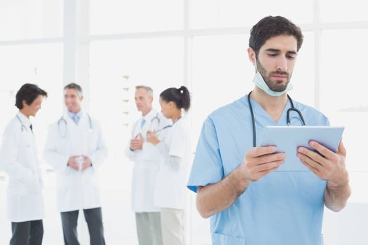 Serious doctor looking at tablet with co-workers behind him