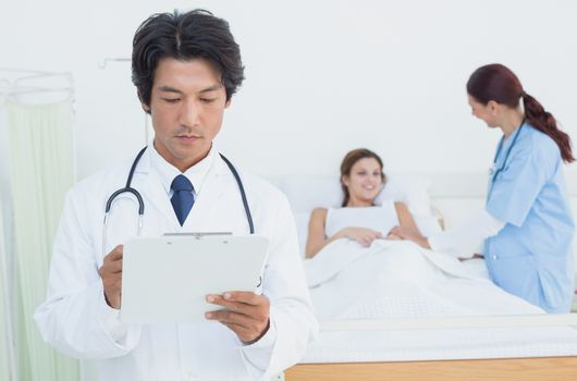 Doctor looking at a chart in front of patient