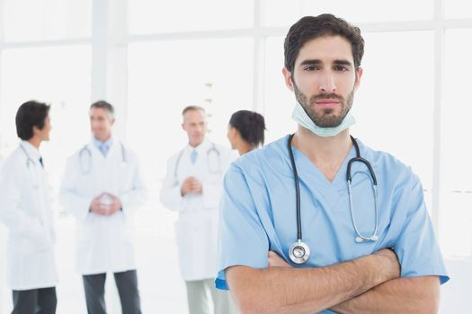 Serious doctor looking at camera with colleagues behind him