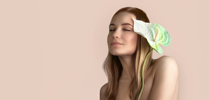 Portrait of a gentle woman with calla flower and closed eyes isolated on beige pink pastel background, genuine beauty, conceptual photo of a spa and wellness, panorama with copy space