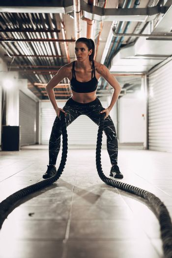 Young muscular woman exercising with ropes at the garage gym. Selective focus.