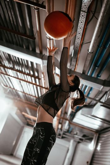 Young muscular woman doing exercise with ball at the garage gym. She have a hard cross training.