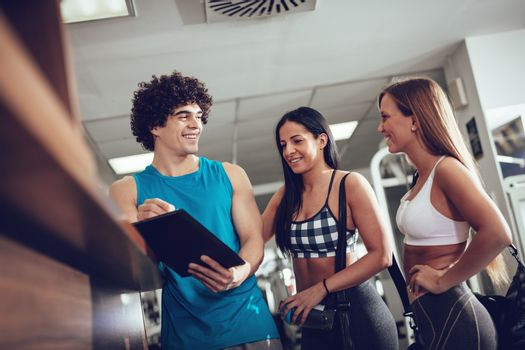 Two happiness female friends consult with fitness instructor before workout at the gym.